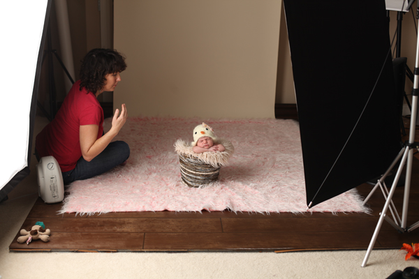 Image of Mom taking a photo of her new born using props